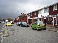 An image of a row of shops on the right side with cars parked in front in a parking area.