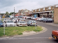 An image of a row of shops showing cars parked in the parking area in front of the shops.