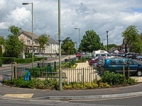 An image of Highlands Road showing the shops on the right hand side, houses on the left hand side and the newly landscaped central parking area in the foreground.