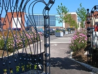 An image of the Market Quay car park showing newly planted trees and flower beds with a metal seat shaped like a crown in the foreground.