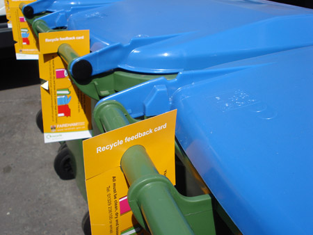 Yellow hangers on recycling bins